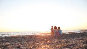 Mamá con dos muchachos, hijos del resto en la playa por el mar en la puesta del sol, metrajes