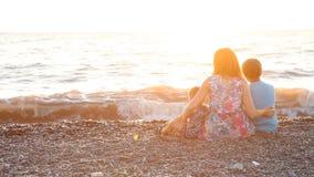 Mamá con dos muchachos que se sientan en una playa con el mar de los hijos en la puesta del sol almacen de video