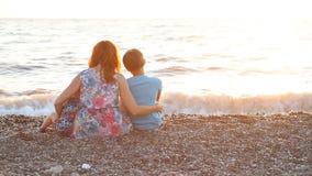 Mamá con dos muchachos que se sientan en una playa con el mar de los hijos en la puesta del sol almacen de metraje de vídeo