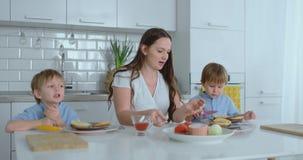 Mamá con dos niños en la cocina en la tabla que prepara la hamburguesa para el almuerzo almacen de metraje de vídeo