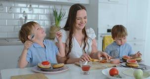Mamá con dos niños en la cocina en la tabla que prepara la hamburguesa para el almuerzo almacen de video