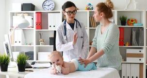Mamá con el bebé de examen del doctor que miente y que juega en la tabla y que discute el tratamiento almacen de video