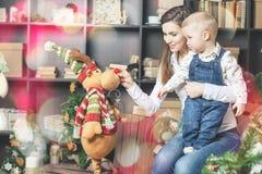 Mamá con el bebé, el regalo de Cristmas y el Año Nuevo Imagen de archivo