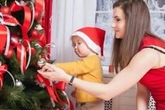 Mamá con el bebé que adorna un árbol de navidad Imagen de archivo libre de regalías