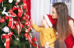 Mamá con el bebé que adorna un árbol de navidad Imagen de archivo