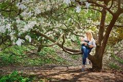 Mamá con el bebé que se sienta en rama de árbol en el jardín florecido de la primavera Foto de archivo libre de regalías