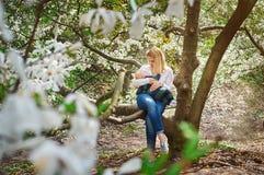 Mamá con el bebé que se sienta en rama de árbol en el jardín florecido de la primavera Imagenes de archivo