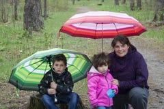 Mamá con el hijo y la hija que se sientan en el bosque debajo de los paraguas Foto de archivo