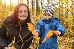 Mamá con el juego del hijo con las hojas de otoño Imagen de archivo libre de regalías