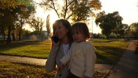 Mamá con el niño en sus brazos que habla en un smartphone y que camina en parque del otoño a la luz de puesta del sol Sentada fel almacen de video
