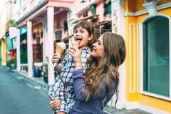 Mamá con el niño que come el helado en calle de la ciudad Imagen de archivo libre de regalías