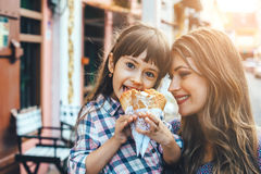 Mamá con el niño que come el helado en calle de la ciudad Imágenes de archivo libres de regalías