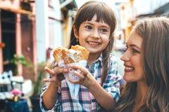 Mamá con el niño que come el helado en calle de la ciudad Imagenes de archivo
