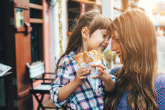Mamá con el niño que come el helado en calle de la ciudad Fotografía de archivo libre de regalías