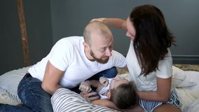 Mamá con el papá y el hijo que juegan junto en cama en casa en el sitio, momentos felices metrajes