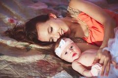 Mamá con la hija en cama Foto de archivo libre de regalías