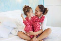 Mamá con la hija en la cama imagenes de archivo