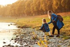 Mamá con la hija en otoño Madre e hija que caminan cerca del río en tiempo del otoño Familia feliz Fin de semana de la caída en e foto de archivo