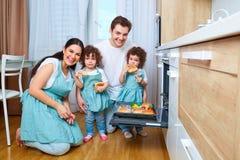 Mamá con la hija rizada en la cocina que se prepara en el lugar El B Fotografía de archivo libre de regalías