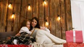 Mamá con la niña que lee un libro y que se relaja en un sofá acogedor bajo luces de la Navidad Foto de archivo libre de regalías