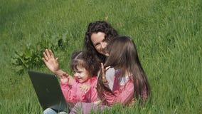 Mamá con las hijas en hierba verde con el ordenador portátil Familia en un parque en un día soleado metrajes