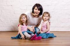 Mamá con las hijas que se sientan en la sala de estar foto de archivo