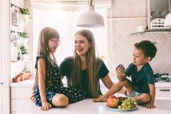 Mamá con los niños que comen en la tabla de cocina fotos de archivo