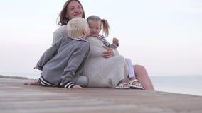 Mamá con los niños que miran el sol ir abajo en el mar metrajes