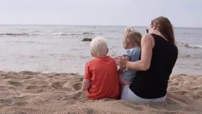 Mamá con los niños que se sientan en la playa por el mar almacen de video