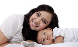 Mamá con su bebé en cama Foto de archivo libre de regalías