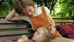 Mamá con su hija, muchacha preescolar que miente en el revestimiento de una mujer joven en el parque en el banco D?a asoleado del metrajes