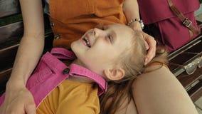 Mamá con su hija, muchacha preescolar que miente en el revestimiento de una mujer joven en el parque en el banco D?a asoleado del almacen de metraje de vídeo