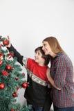 Mamá con su hijo que pone los ornamentos en el árbol de navidad Imagenes de archivo