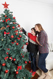 Mamá con su hijo que pone los ornamentos en el árbol de navidad Imagen de archivo libre de regalías