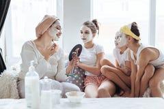 Mamá con sus hijas que hacen la mascarilla de la arcilla Imagen de archivo