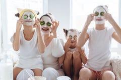 Mamá con sus hijas que hacen la mascarilla de la arcilla Foto de archivo libre de regalías