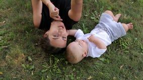 Mamá con un bebé recién nacido que miente en la hierba verde y el parque en el verano metrajes