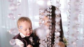 Mamá con un hijo de un año que juega con los cristales de la lámpara en casa almacen de metraje de vídeo
