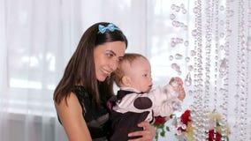 Mamá con un hijo de un año que juega con los cristales de la lámpara en casa almacen de video