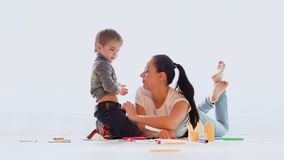 Mamá con un juego y un drenaje del niño pequeño en el cuarto almacen de metraje de vídeo