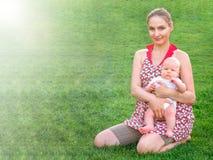 Mamá con un niño en un césped verde foto de archivo libre de regalías