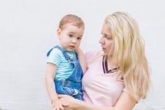 Mamá con un niño en sus brazos contra la pared Imagen de archivo