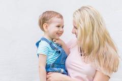 Mamá con un niño en sus brazos contra la pared Foto de archivo