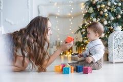 Mamá con un pequeño hijo cerca de un árbol hermoso en su casa que juega con los cubos coloreados Fotografía de archivo