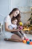 Mamá con un pequeño hijo cerca de un árbol hermoso en su casa que juega con los cubos coloreados Imagen de archivo