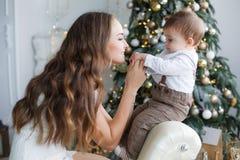 Mamá con un pequeño hijo cerca de un árbol de navidad hermoso en su casa Foto de archivo