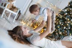Mamá con un pequeño hijo cerca de un árbol de navidad hermoso en su casa Imagenes de archivo