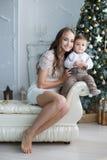 Mamá con un pequeño hijo cerca de un árbol de navidad hermoso en su casa Foto de archivo libre de regalías