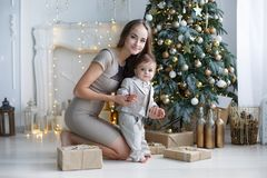 Mamá con un pequeño hijo cerca de un árbol de navidad hermoso en su casa Imagen de archivo