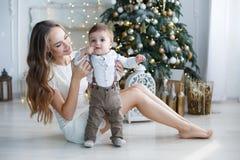 Mamá con un pequeño hijo cerca de un árbol de navidad hermoso en su casa Fotografía de archivo libre de regalías
